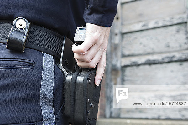 Close up of a female police woman drawing handgun from holster.