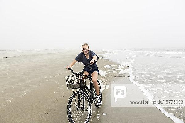 Teenagerin beim Fahrradfahren auf Sand am Strand