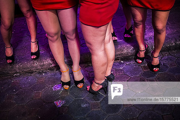 High angle view of small group of women wearing red miniskirts and high heels standing on street at night.