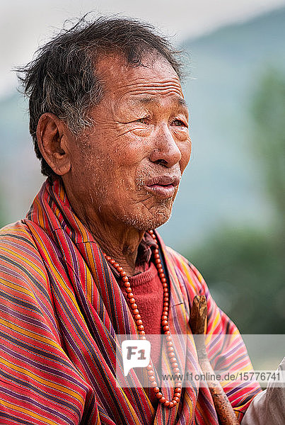 Portrait elderly Bhutanese man wearing prayer beads  Bhutan  Asia