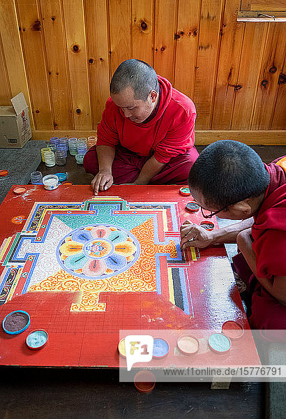 Buddhist monks making a diorama (mandala) with coloured sand  which once made is wiped off to demonstrate transience and impermanence  Bhutan  Asia