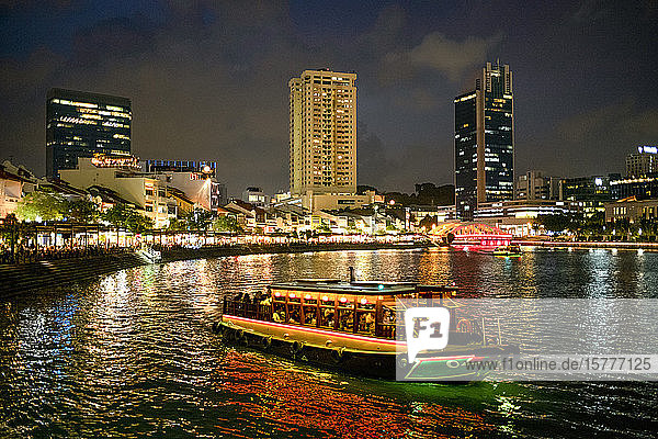 Tourist boat near the historic Boat Quay in Singapore river at dusk  Singapore  Southeast Asia  Asia