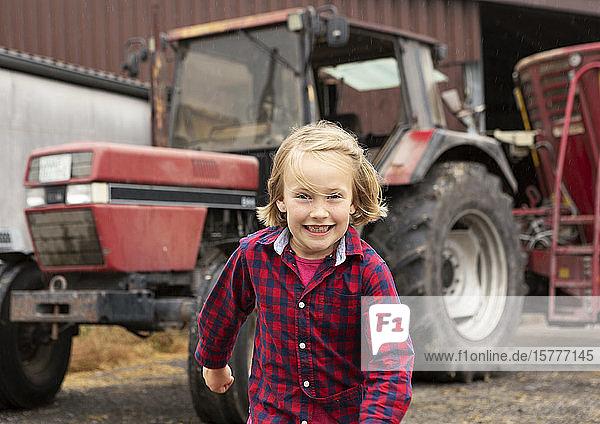 Mädchen auf einem Bauernhof  Landmaschine im Hintergrund
