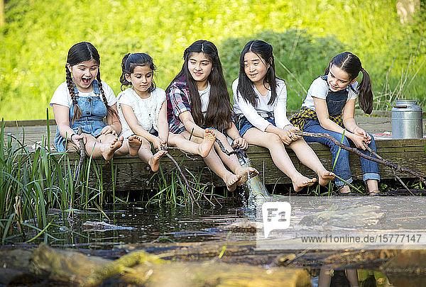 Fünf Kinder aus verschiedenen Nationen spielen an einem Teich