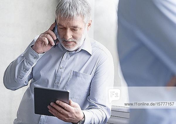 Geschäftsmann schaut auf Tablet-PC