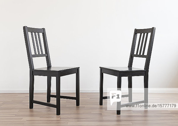 Zwei Stühle stehen Rücken an Rücken Zwei Stühle stehen Rücken an Rücken