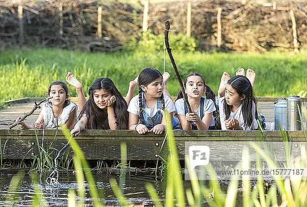 Fünf Kinder aus verschiedenen Nationen spielen an einem Teich Fünf Kinder aus verschiedenen Nationen spielen an einem Teich