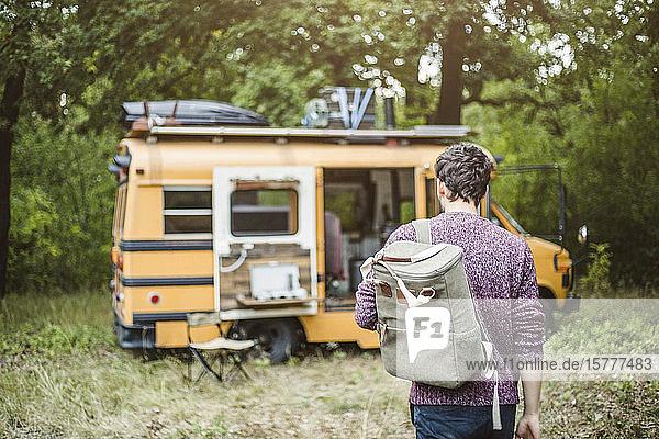 Rückansicht eines jungen Mannes  der während des Campens mit Rucksack in Richtung Wohnmobil im Wald läuft