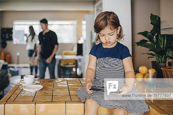 Tochter telefoniert  während die Eltern im Hintergrund stehen