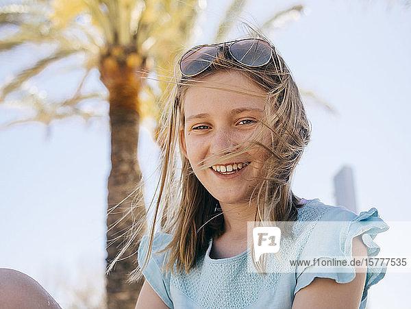 Porträt eines lächelnden Mädchens  das gegen den Himmel sitzt