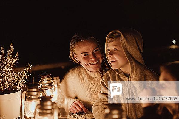 Lächelnde Mutter schaut Kinder an  während sie im Restaurant am Tisch sitzt