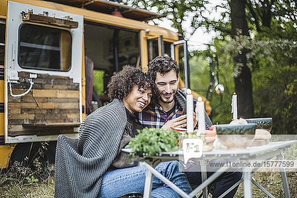 Lächelndes junges Paar  das sich beim Zelten im Wald gemeinsam ein Handy teilt  während es in eine Decke gehüllt ist