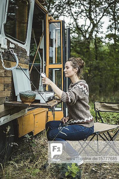 Frau in voller Länge  die während des Zeltens im Wald Kaffee auf dem Herd eines Wohnmobils zubereitet