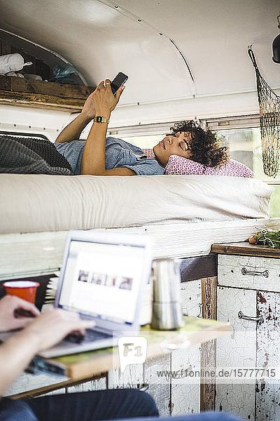 Junge Frau liegt im Bett  während sie ein Mobiltelefon benutzt  von Mann mit Laptop im Wohnwagen