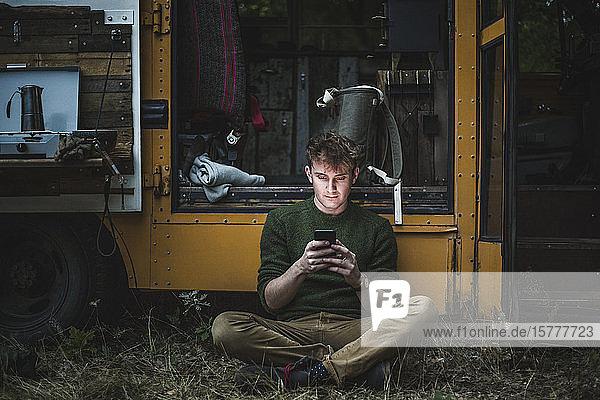 Mann sitzt im Schneidersitz  während er ein Smartphone gegen ein Wohnmobil beim Camping benutzt