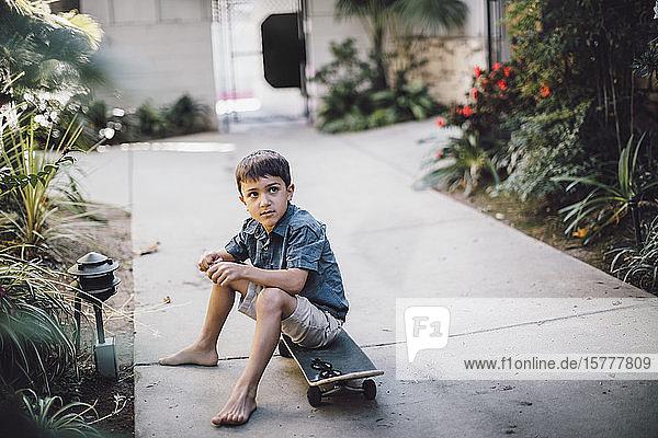 Junge schaut weg  während er auf dem Fußweg über dem Skateboard sitzt