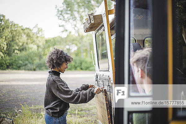 Side view of smiling woman adjusting wood on caravan door during camping in forest