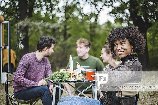 Porträt einer lächelnden Afro-Frau  die beim Camping im Wald mit Freunden am Tisch sitzt