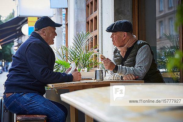 Homosexuelles Paar isst Essen  während es in einem Straßencafé in der Stadt sitzt