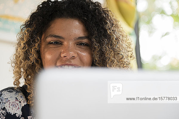 Smiling woman behind laptop