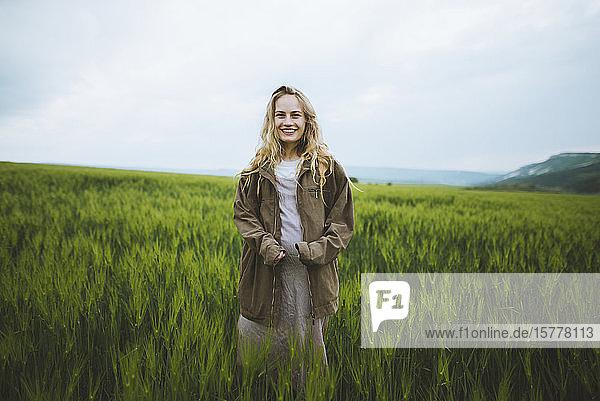 Smiling woman wearing jacket in field in Crimea  Ukraine