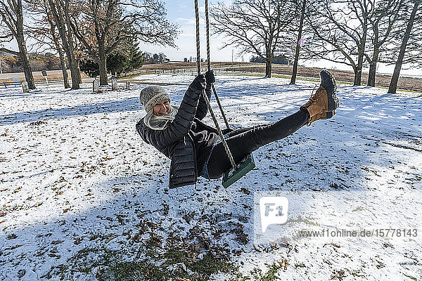 Smiling woman on swing in snow