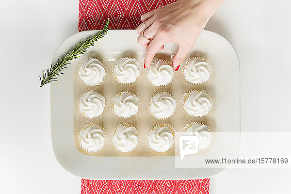 Woman's hand reaching for cupcake on tray