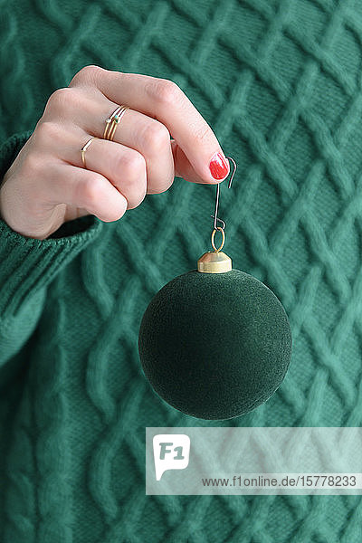 Woman wearing green holding green bauble
