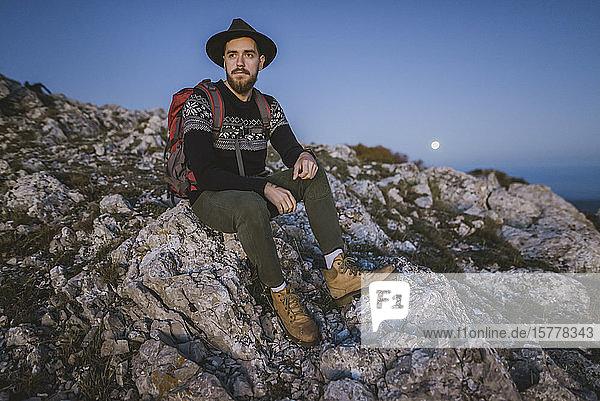 Man sitting on rock at sunset