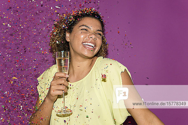 Smiling woman holding champagne glass under confetti