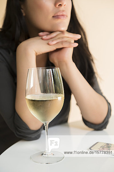 Woman at table by smart phone and glass of wine