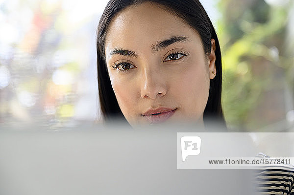 Frau mit schwarzen Haaren hinter Laptop