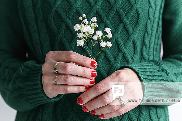 Woman wearing green holding white flowers