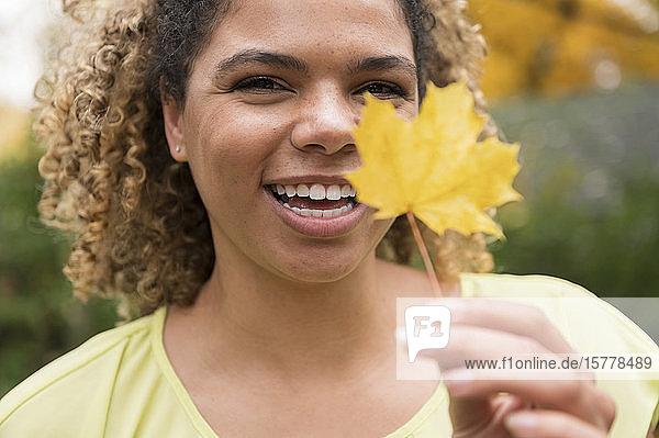 Lächelnde Frau hält Herbstblatt