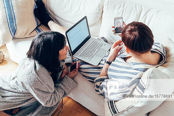Frauen entspannen sich am Laptop auf dem Sofa