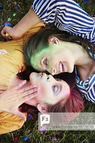Two young women covered in coloured chalk powder lying on grass at Holi Festival  overhead view
