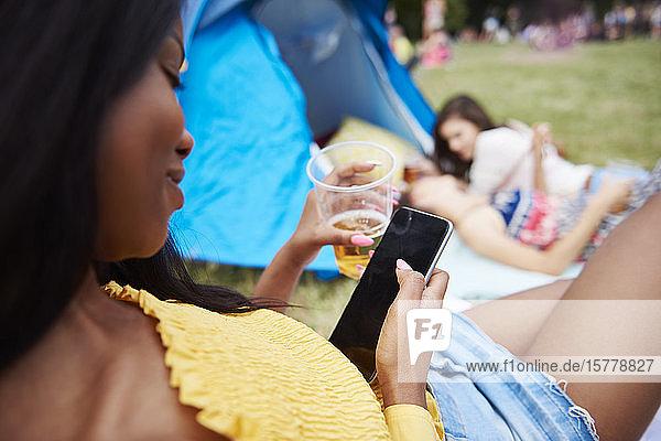 Frau benutzt Handy beim Musikfestival  Freunde im Hintergrund