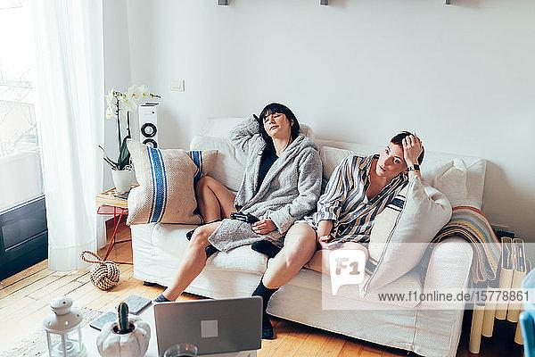Women in nightwear relaxing on sofa