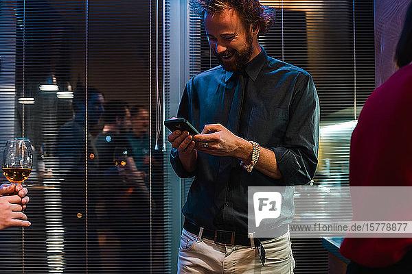 Mann benutzt Mobiltelefon auf Party in Wohnung