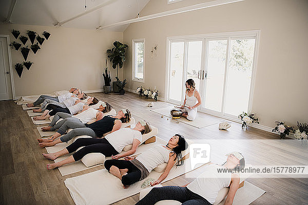 Frauen in Entspannungsstellung posieren nach Yoga-Unterricht auf Rückzug