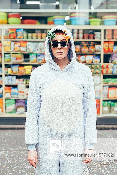 Porträt einer Frau  die einen Erwachsenen-Bodysuit und eine neuartige Sonnenbrille trägt und in die Kamera schaut