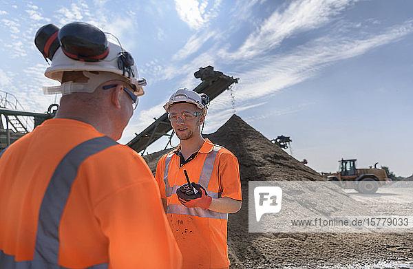 Arbeiter im Gespräch in einer Betonrecyclinganlage