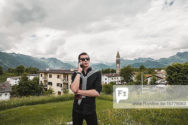 Ein Geschäftsmann in einem Bergdorf telefoniert mit einem Smartphone  Francenigo  Venetien  Italien