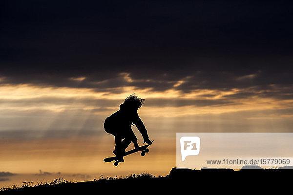 Junge Bursche beim Skateboarden bei Sonnenuntergang  beim Springen  in der Luft  Doolin  Clare  Irland