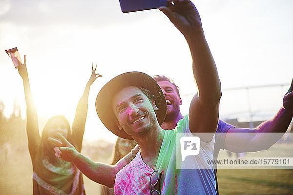 Vier junge erwachsene Freunde mit farbigem Kreidepulver bedeckt beim Holi-Fest