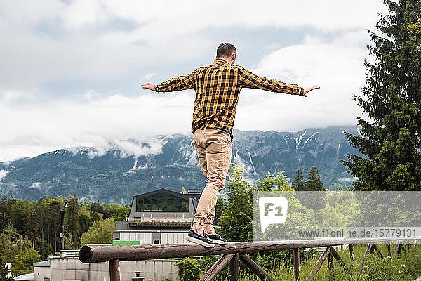 Mann balanciert auf einem Holzzaun in einem Bergdorf  Dolenci  Slowenien