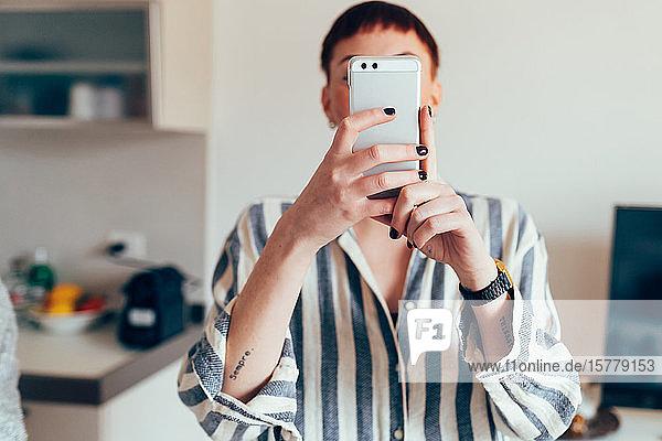 Frau nimmt Selfie am Mobiltelefon  Gesicht verdunkelt