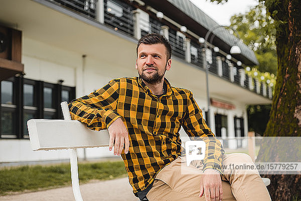 Mann sitzt auf Parkbank vor dem Hotel  Dolenci  Slowenien