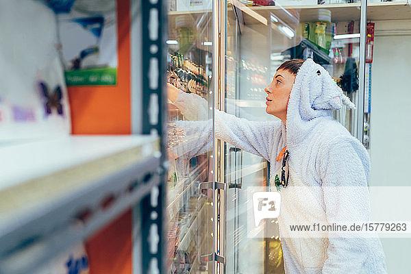 Frau im Erwachsenen-Bodysuit beim Einkaufen im Supermarkt