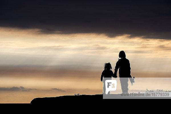 Bruder und Schwester  die Hand in Hand gehen  bei Sonnenuntergang  Doolin  Clare  Irland